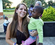 Grace Fisher at the Mompang Babies' Home in Ghana. Bishop Fisher is in the background.