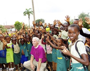 Bishop Fisher surrounded by gleeful children from St. Justin's School in Ghana.
