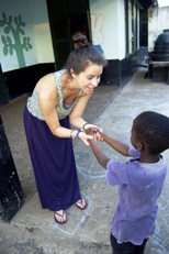Caragh Fisher holds hands with a new friend at the Mompang Babies' Home in Ghana.